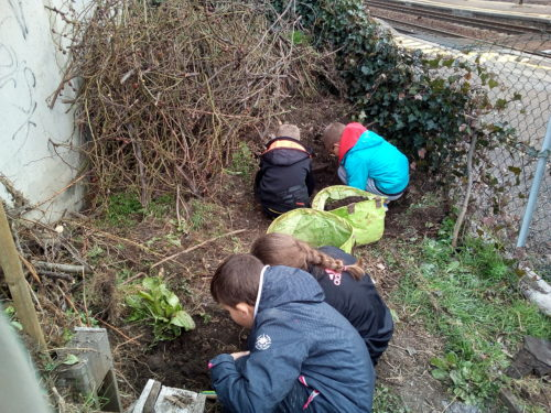 les enfants cherchent des verres de terre dans le composte