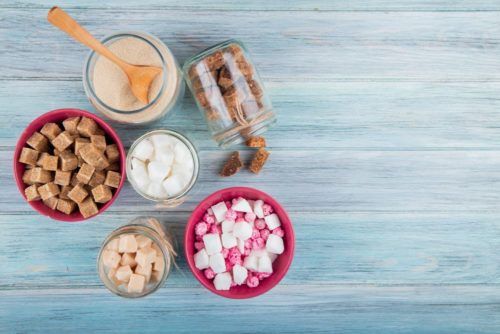 top view of different types of sugar in glass jars on rustic background with copy space