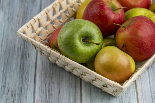 side view colored apples in a basket on a gray background