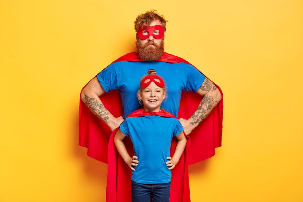 Photo of confident ginger father and daughter keep hands on waists, pretend being superhero and defend people, wear special costumes, isolated on yellow background. Family team ready to work
